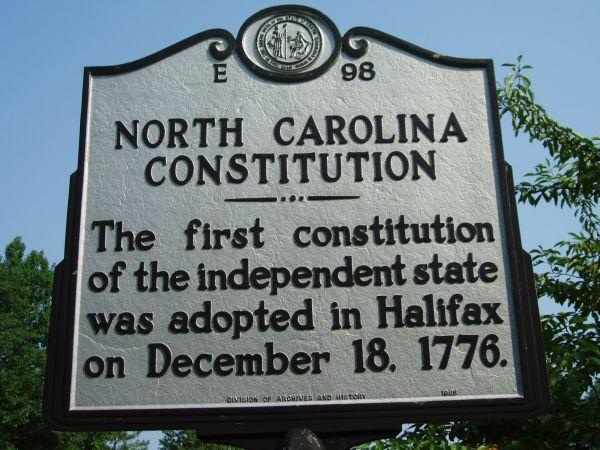 """This is an image of the North Carolina Highway historical marker number E-98 located in Halifax County. The text reads: """"The first constitution of the independent state was adopted in Halifax on December 18, 1776."""