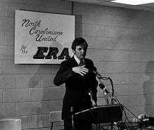 """The photo shows Alda at a podium with a sign behind him reading, """"North Carolinians United for the ERA."""""""