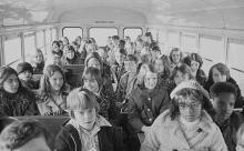 Two African American children and more than thirty white children riding in a school bus from the suburbs to an inner city school, Charlotte, North Carolina (1973).