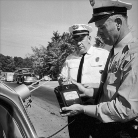 Chapel Hill police officers calibrating a speed-detection device in 1961. Photograph by Roland Giduz. North Carolina Collection, University of North Carolina at Chapel Hill Library.